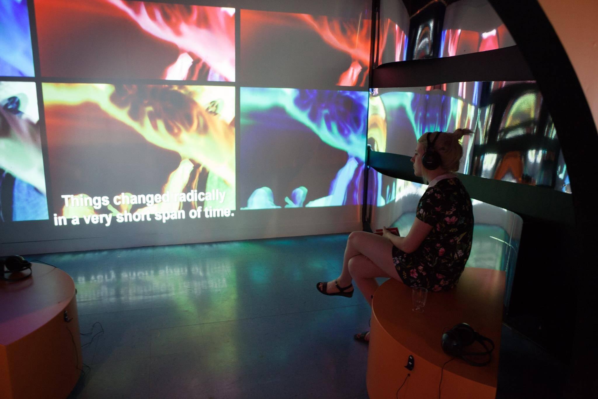 Une femme est assise dans une salle immersive et regarde des projection d'images sur un mur