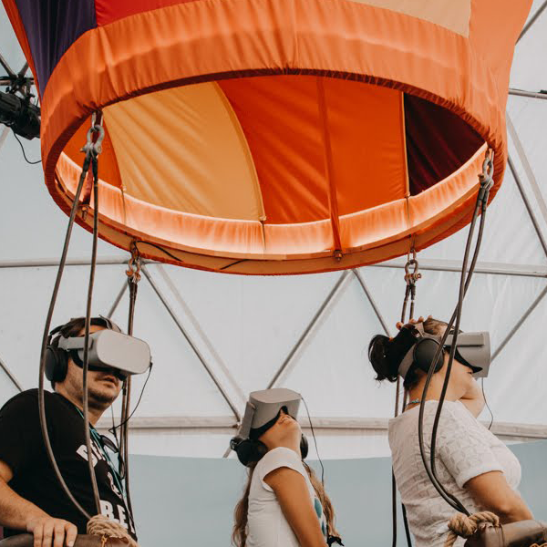 Three people living a VR experience in an interior hot air baloon