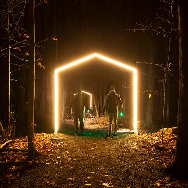 Des gens marchent la nuit dans un sentier à travers une arche illuminée en forme de maison