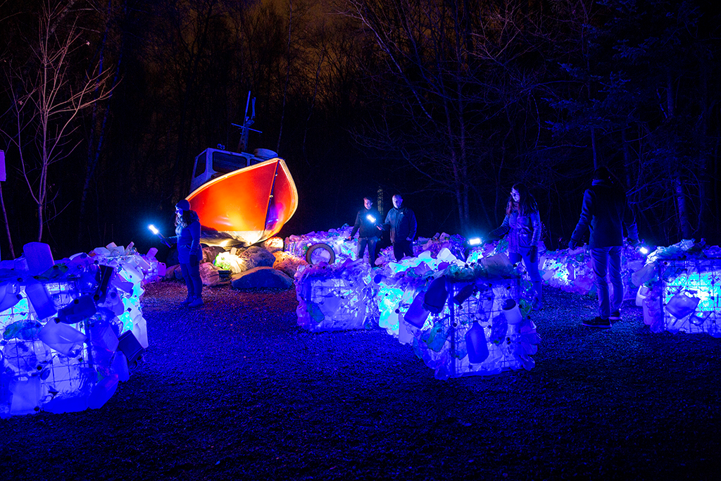 People exploring an illuminated art installation, which looks like a boat and islands of plastic bottles, on the edge of the forest at night