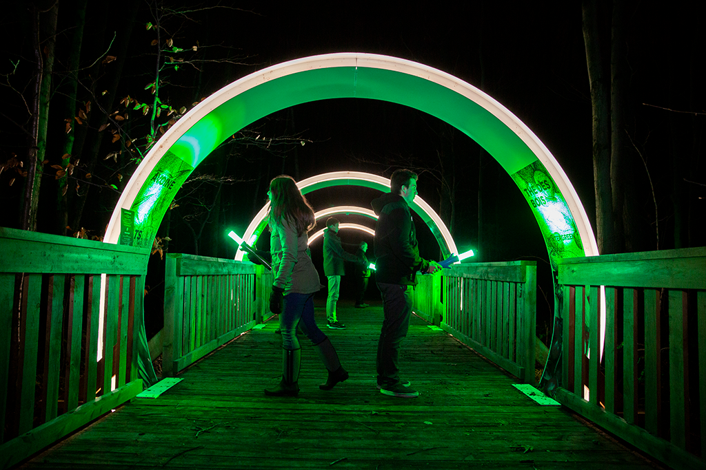 People reading information on a tunnel wall while going through a green illuminated tunnel on a wooden path at night