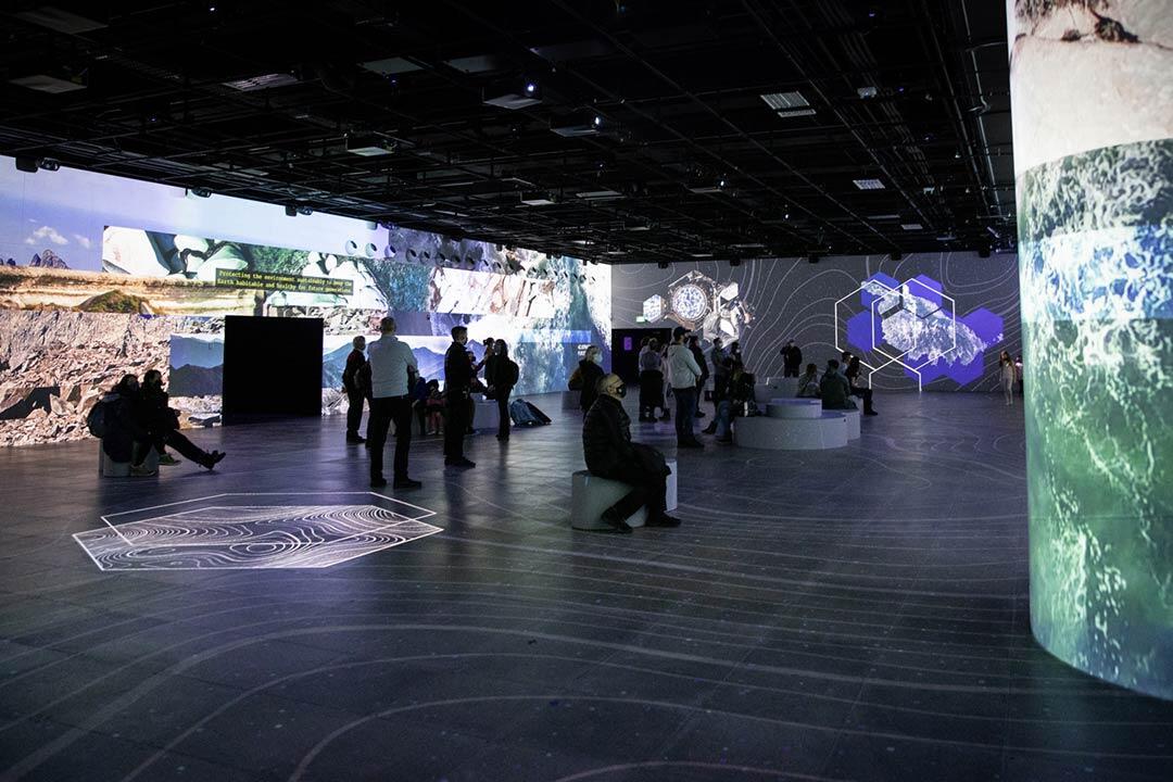 Gens qui sont dans une grande salle immersive, des images sont projetées sur les murs et le plancher