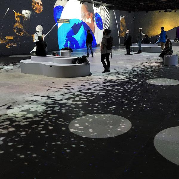 Gens dans la salle immersive où des images sont projetées sur les murs et sur le plancher